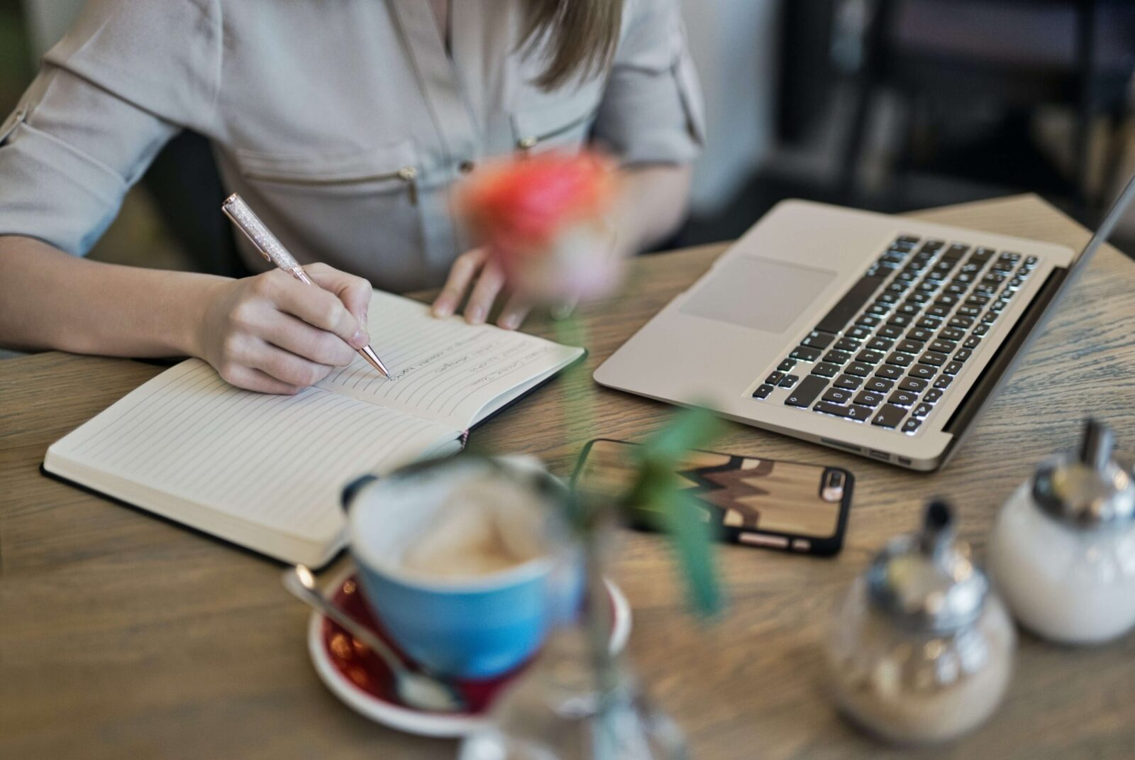 woman's hand writing in a notebook on a table with laptop and coffee mug