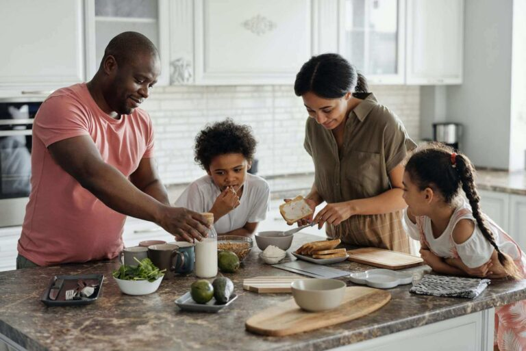 mom, dad, and two children smiling and making food in the kitchen