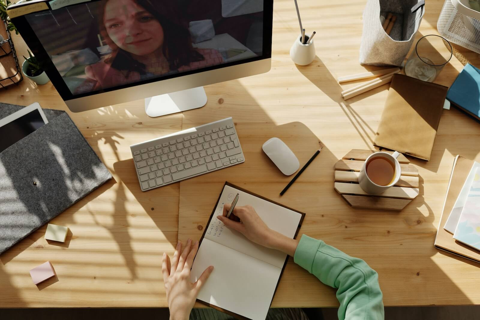 person writing in a notebook on a table while on a video call with a woman