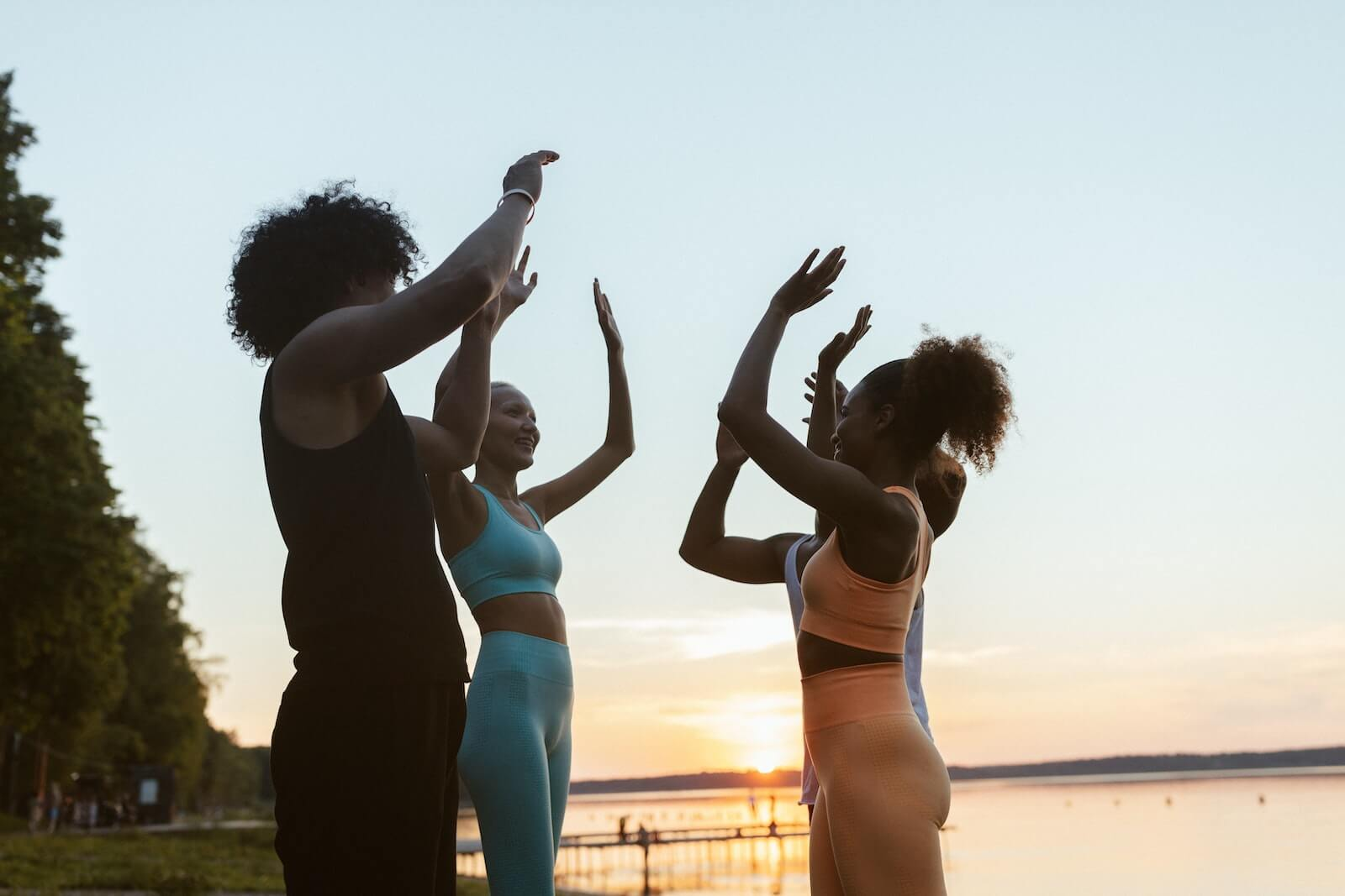 Group of women in exercise clothes standing in a circle outside high fiving